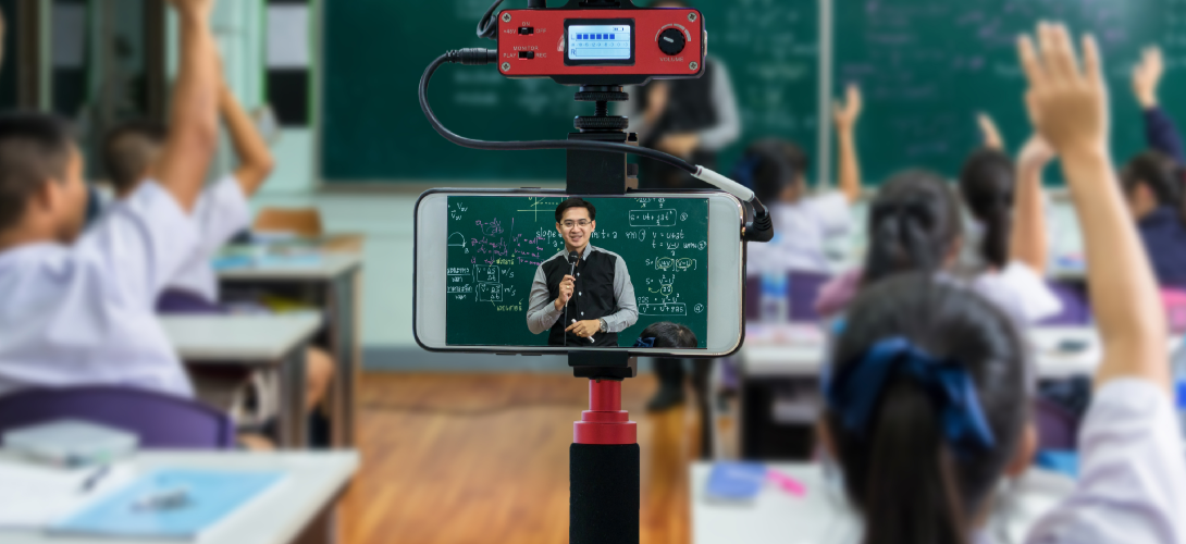 A teacher records his classroom for students who use video conferencing technology for digital learning.