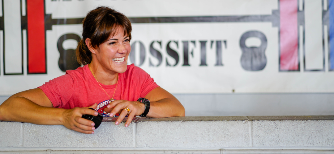 Danielle Williams, owner of Mount Vernon CrossFit, leans against a wall at their Alexandria, Virginia location.