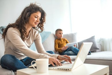 A woman works at her laptop while her son uses a tablet