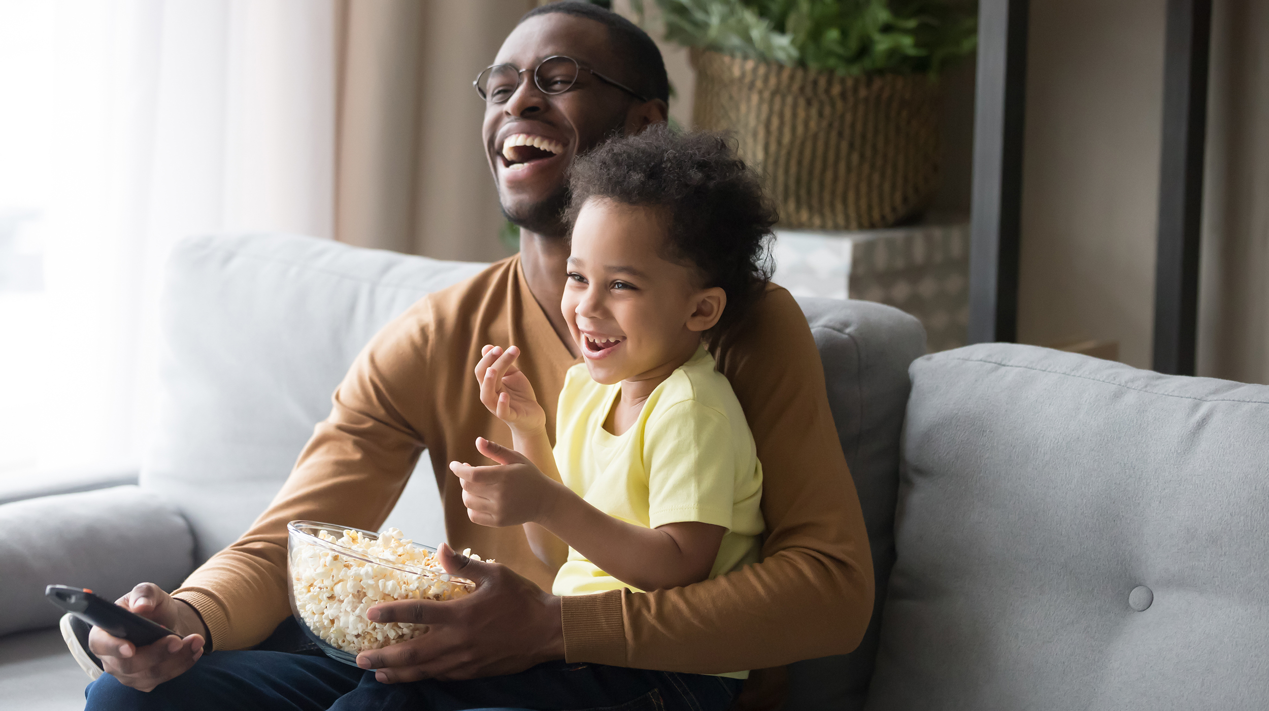 Father and child laugh together while watching a tv show