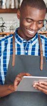 A man in his shop entering information into his tablet