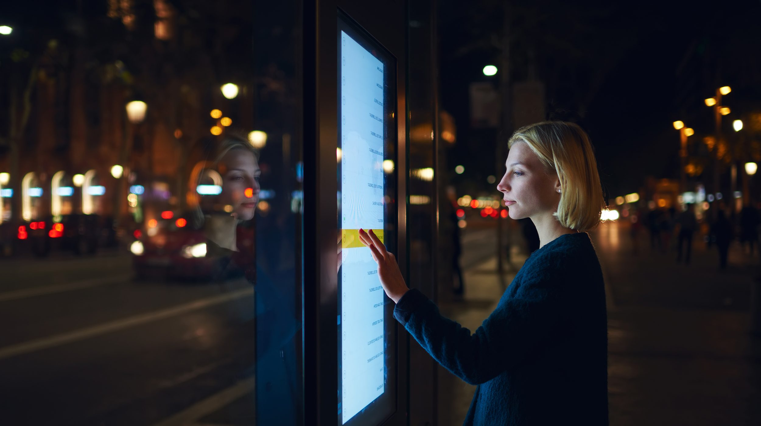 A woman selects information on a transit system dashboard