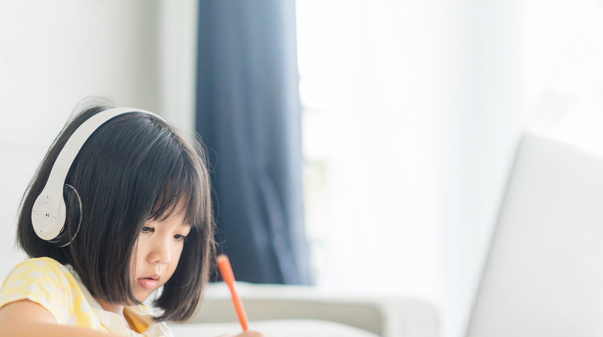 A young girl learning remotely on a laptop