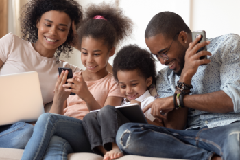 Family on a couch using multiple Wi-Fi enabled devices.