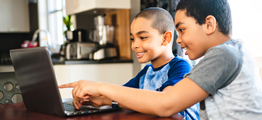 Two young boys on a laptop.