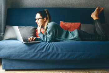 A female college student attends an online class from her couch.