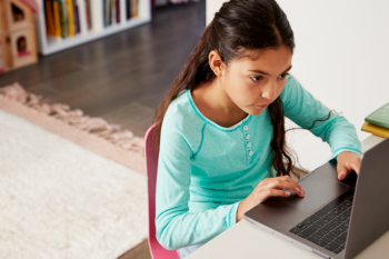 Young girl at home using a laptop computer.