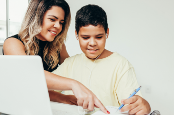 A mother helps her young son complete schoolwork on a laptop.