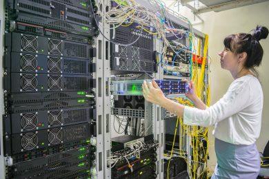 A woman installs a new server in a modern data center.