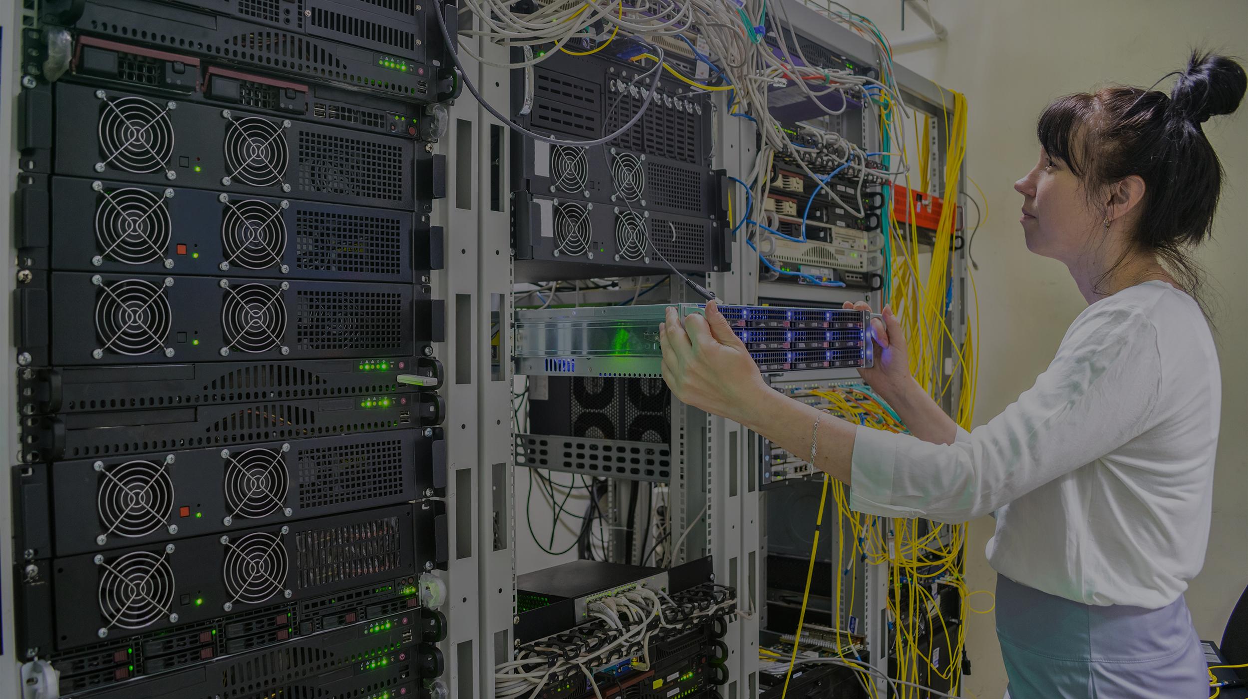 A woman installs a new server in a modern data center